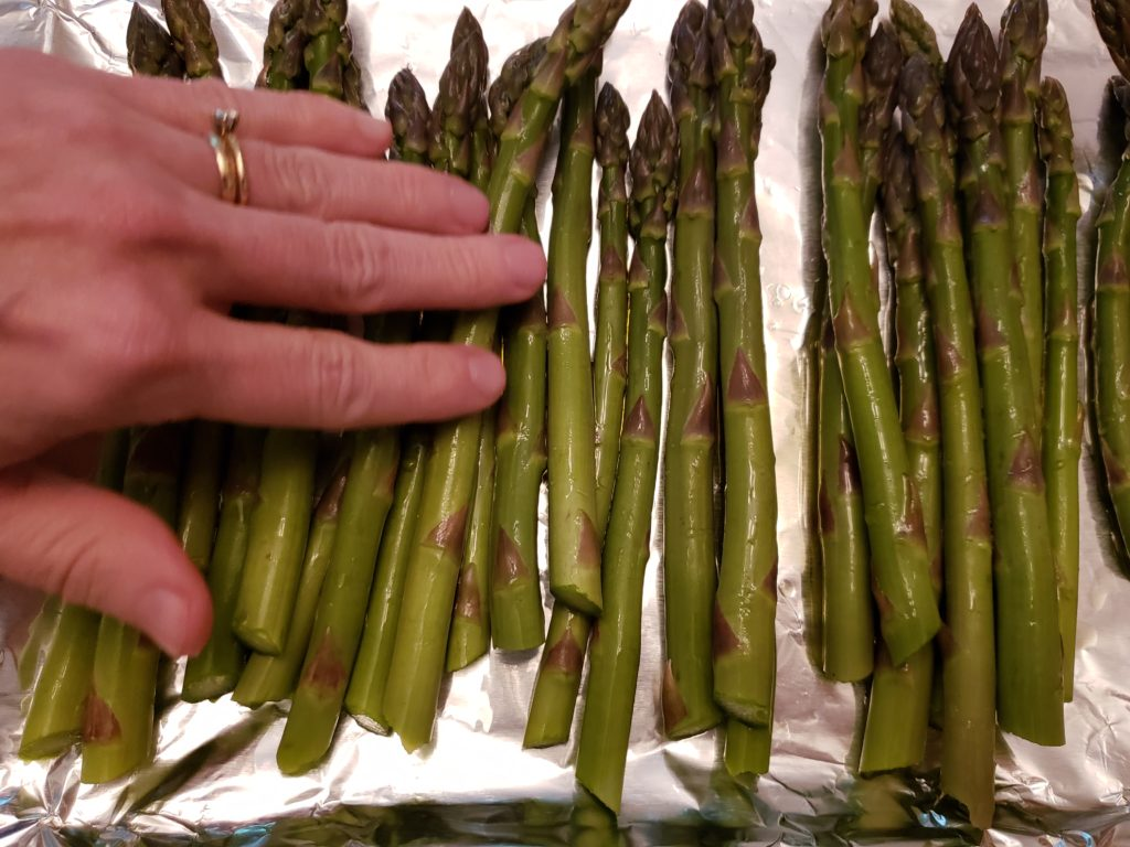 rubbing olive oil onto asparagus