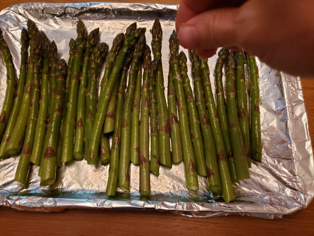 asparagus on baking sheet being sprinkled with seasonings