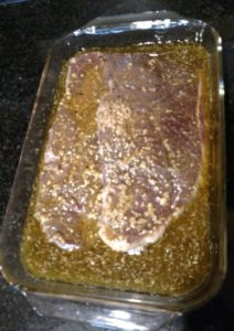 meat and marinade in glass baking dish