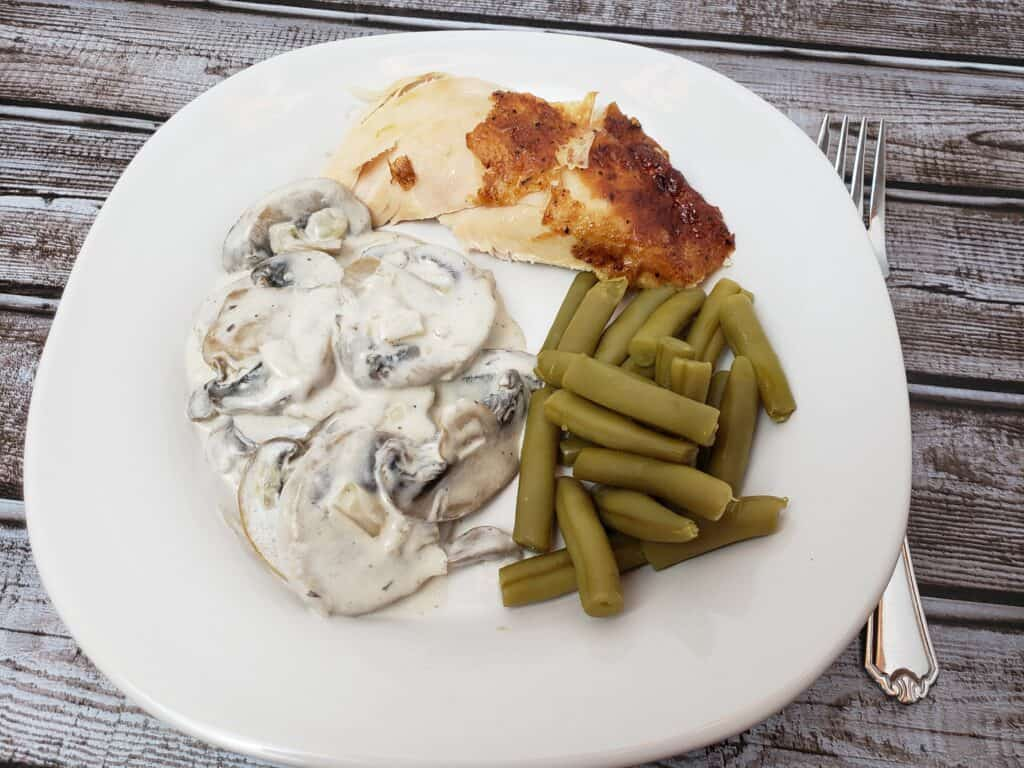 Creamed Mushrooms, rotisserie chicken and green beans on white plate