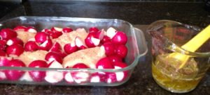 chicken and radishes in baking dish and marinade in measuring cup