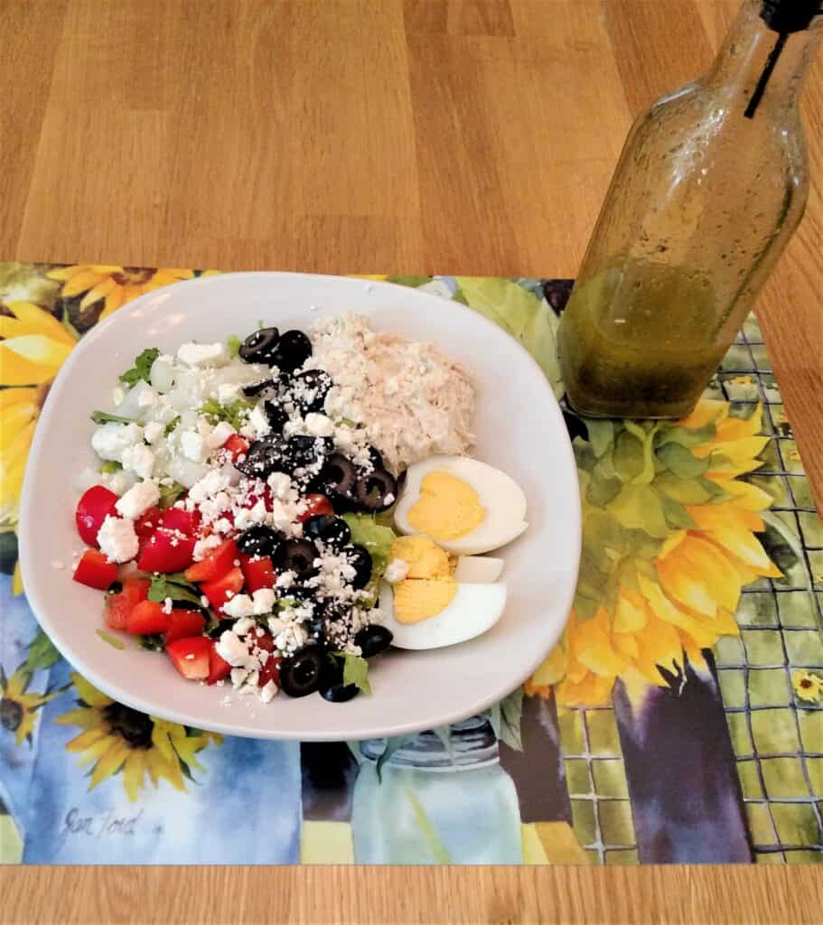 Homemade Italian Dressing Dry Mix on a salad pictured on a pretty sunflower mat