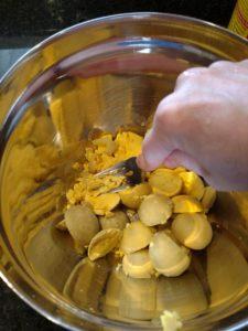 mashing egg yolks in bowl with fork
