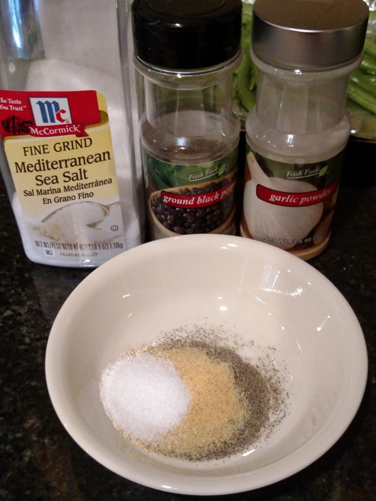 salt, pepper and garlic powder in bowl and bottles behind it