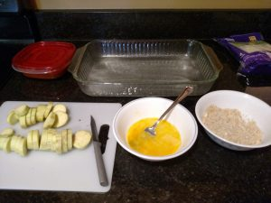 sliced eggplant on left, bowl with egg in middle, bowl with breading on right
