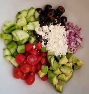 Ingredients for Greek Cucumber Avocado Salad in a bowl
