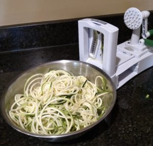 zoodles in bowl next to spiralizer
