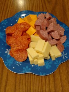 white and orange cheese cubed, cubed salami and pepperoni slices on blue plate