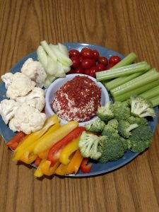 cheeseball in middle of platter with vegetables around it