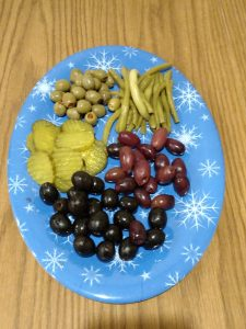 different olives and pickles on blue plate