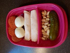 Pepperoni, hard boiled egg, lunchmeat chicken, cheese and mustard rolled up, pickle and macadamia nuts