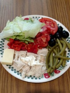 lettuce, tomato, black olives, pickled green beans, chicken and block of cheese on plate
