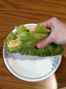 lunch wrap made with lettuce leaf, turkey lunchmeat, shredded cheese and mayo with a bite out of it.