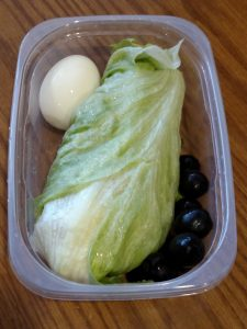lunch wrap made with lettuce leaf, turkey lunchmeat, shredded cheese and mayo in a container with a hard boiled egg and a few black olives