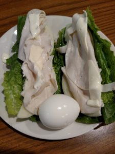 romaine lettuce leaves, cheese and turkey lunchmeat to roll into a sandwich wrap and hard boiled egg on a plate