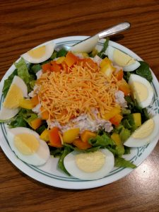 salad with hard boiled egg quarters around the edges and shredded cheese on top