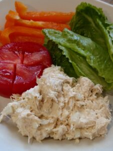 chicken salad with tomato, lettuce and orange bell pepper