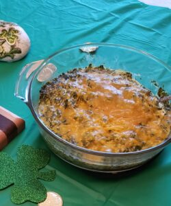 creamy spinach cheese bake with cheddar cheese on top in glass bowl on green table cloth