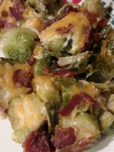 cheesy brussels sprouts with bacon pieces on top