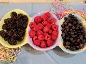 black, raspberries and blueberries in easter dish