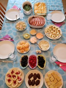 plates of dinner and dessert on Easter tablecloth and table set for 4