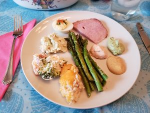 Easter meal on pretty blue tablecloth with Easter eggs on it