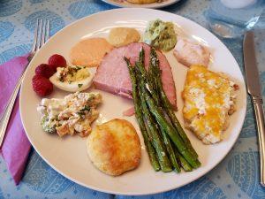 Easter dinner plate; ham, deviled eggs, asparagus, bun, etc.