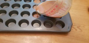 pouring peanut butter mixture into fat bomb molds