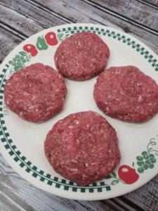 4 raw hamburgers on a plate