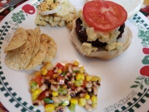 hamburger with onion relish, tomato next to corn and red pepper salsa and chips and potato salad